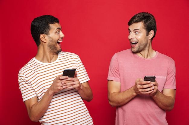 Twee vrolijke mannenvrienden die zich geïsoleerd over rode muur bevinden, die mobiele telefoons gebruiken