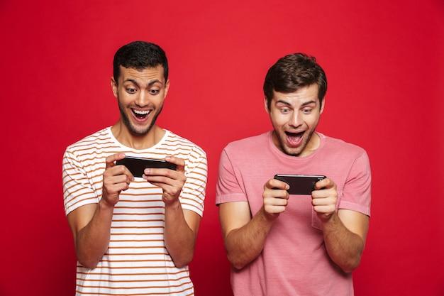 Twee vrolijke mannenvrienden die zich geïsoleerd over rode muur bevinden, spelen op mobiele telefoons