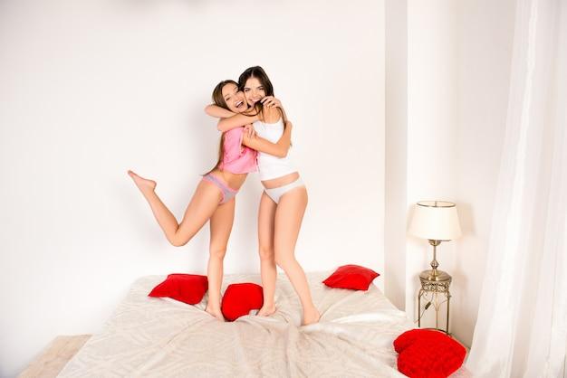 Twee vrolijke meisjes in pyjama's dansen op het bed en knuffelen
