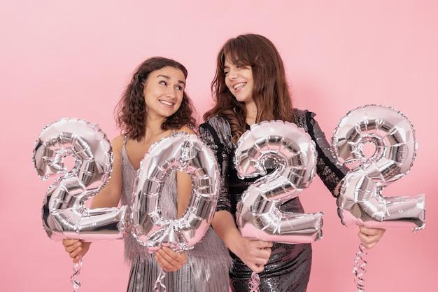 Twee vrolijke meisjes met zilveren folieballonnen in de vorm van cijfers