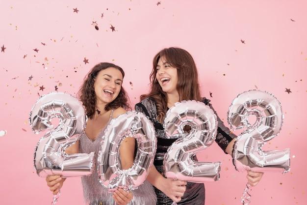 Twee vrolijke meisjes op een roze achtergrond onder confetti houden zilveren folieballonnen met nummers 2022 vast.
