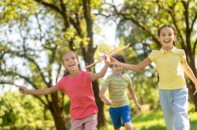Twee vrolijke meisjes rennen met speelgoed en jongen