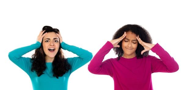 Twee vrolijke meisjes van vrouwenvrienden die op een witte achtergrond worden geïsoleerd