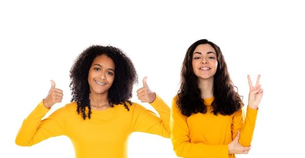 Twee vrolijke meisjes van vrouwenvrienden in gele kleren die op een witte achtergrond worden geïsoleerd