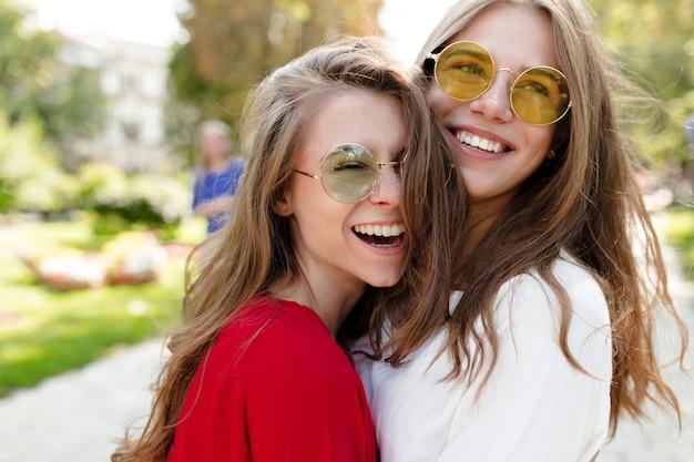 Twee vrolijke mooie meisjes die buiten in zonnige ochtend plezier hebben op stadszicht. stijlvolle modieuze meisjes in heldere zonnebril knuffelen. gelukkige tijd, mode, ontspanning