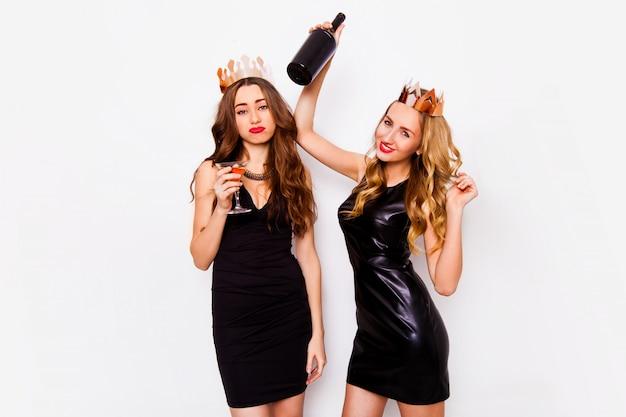 Twee vrolijke mooie vrienden die nieuwjaar of verjaardagsfeest vieren, plezier hebben, alcohol drinken, dansen. emotionele gezichten. elegante vrouwen die de binnen witte achtergrond van het studioportret stellen.