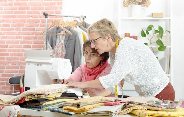Twee vrolijke naaisters die samenwerken in hun werkplaats