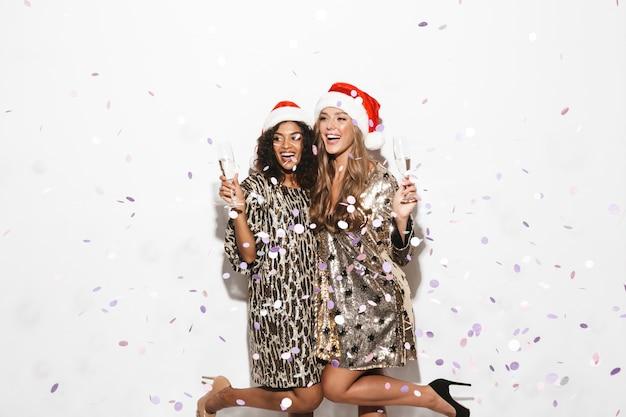 Twee vrolijke netjes geklede meisjes die rode hoeden dragen die nieuwjaar vieren dat over witte ruimte wordt geïsoleerd