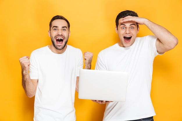 Twee vrolijke opgewonden mannenvrienden die lege t-shirts dragen die geïsoleerd over gele muur staan, laptopcomputer gebruiken, succes vieren