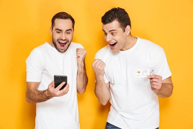 Twee vrolijke opgewonden mannenvrienden die lege t-shirts dragen die geïsoleerd over gele muur staan, naar mobiele telefoon kijken, succes vieren