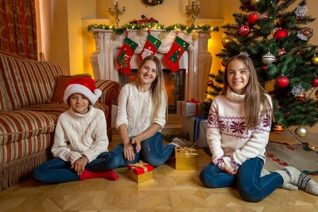 Twee vrolijke schattige meisjes met jonge moeder zitten bij de open haard in de woonkamer ingericht voor kerstmis