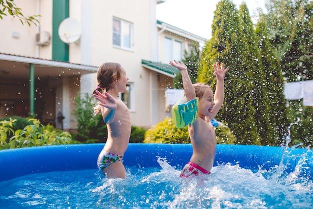 Twee vrolijke schattige zusjes spelen en plezier maken, spetteren en springen in opblaasbaar zwembad in de achtertuin.