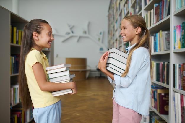 Twee vrolijke schoolkinderen die stapels boeken in hun handen houden