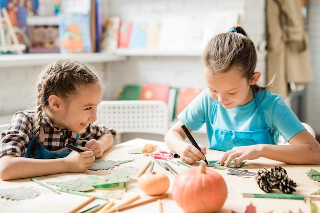 Twee vrolijke schoolmeisjes in vrijetijdskleding zitten bij een bureau terwijl ze tijdens de les over kerstversieringen werken