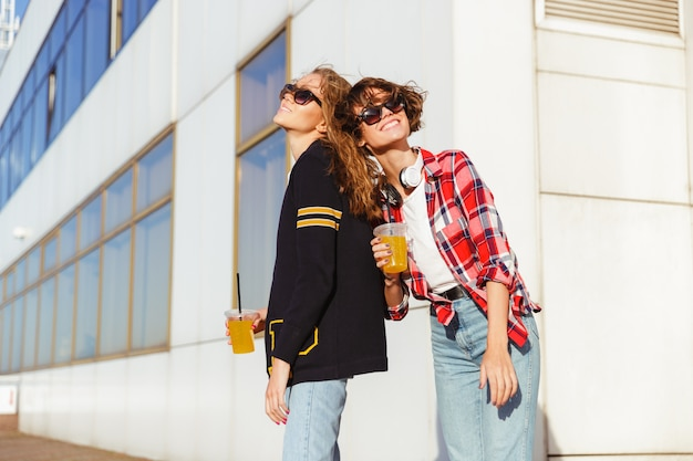 Twee vrolijke tienermeisjes in zonnebril drinken