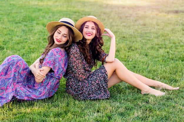 Twee vrolijke tweeling zittend op groene weide en geniet van tijd samen.