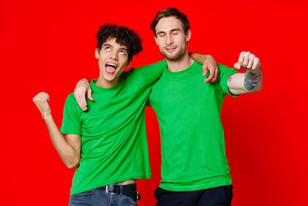 Twee vrolijke vrienden knuffelen groene tshirts emoties communicatie rode achtergrond