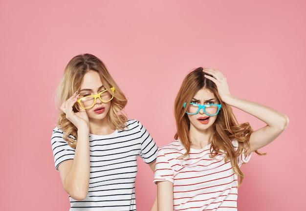 Twee vrolijke vriendinnen in gestreepte t-shirts staan naast elkaar op een roze achtergrond