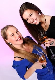 Twee vrolijke vriendinnen met kleurrijke cocktails