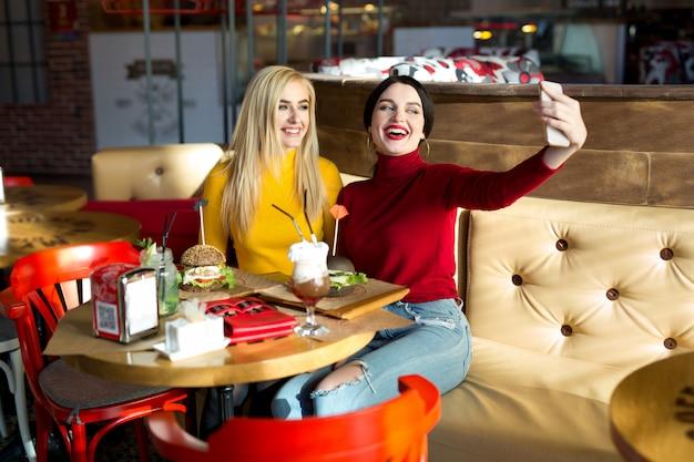 Twee vrolijke vrolijke meisjes nemen een selfie zittend samen in café