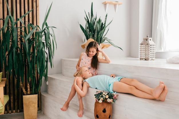 Twee vrolijke vrouwelijke kinderen met blije gezichtsuitdrukking die en in witte binnenlandse ruimte koesteren stellen