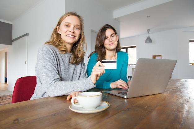 Twee vrolijke vrouwelijke klanten die online betalen