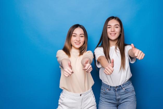Twee vrolijke vrouwen beduimelt omhoog geïsoleerd op blauwe muur. mensen levensstijl concept. bespreek kopie ruimte. duimen opdagen