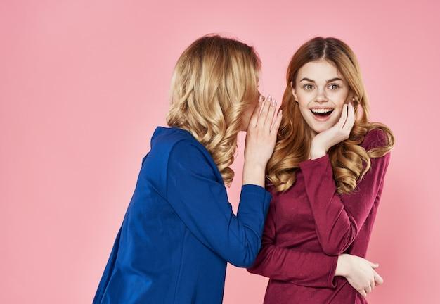 Twee vrolijke vrouwen die de elegante roze achtergrond van de stijllevensstijl communiceren
