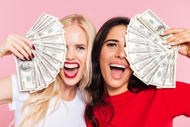 Twee vrolijke vrouwen die hun halve gezichten bedekken en de camera met open mond over roze bekijken