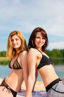 Twee vrolijke vrouwen die rijtjes op het strand stellen