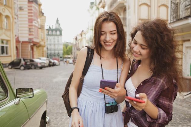 Twee vrolijke vrouwen glimlachen, onderzoekend een kaart op slimme telefoon, die samen reizen