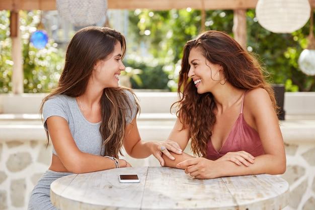 Twee vrolijke vrouwen hebben informele ontmoeting in een coffeeshop, in een goed humeur, vertellen elkaar het laatste nieuws