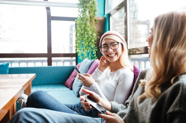 Twee vrolijke vrouwen met behulp van mobiele telefoons en lachen in café