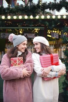 Twee vrolijke vrouwen met cadeautjes op kerstmarkt