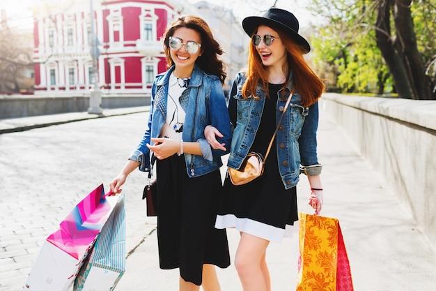 Twee vrolijke vrouwen winkelen in de stad, wandelen in de straten