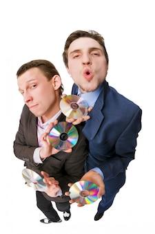 Twee vrolijke zakenlieden die dvd's te koop aanbieden
