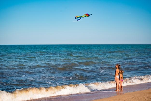 Twee vrolijke zusjes spelen met een vlieger die op de zanderige kust bij de zee loopt
