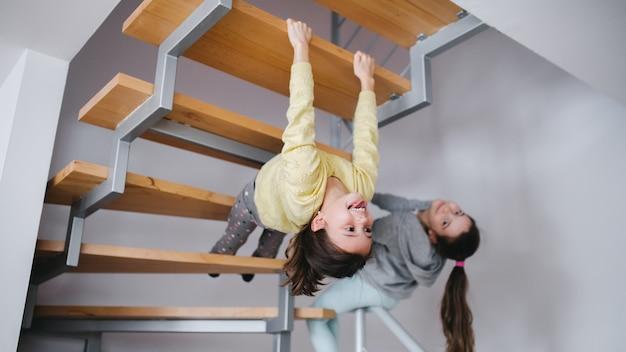 Twee vrolijke zusjes van kleine meisjes binnenshuis, die plezier hebben onder de trap.