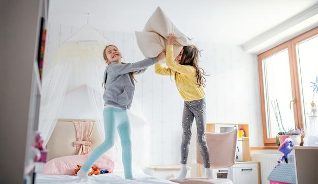 Twee vrolijke zusjes van kleine meisjes binnenshuis, kussengevecht op bed in de slaapkamer.