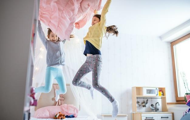 Twee vrolijke zusjes van kleine meisjes binnenshuis, springen op bed in de slaapkamer.