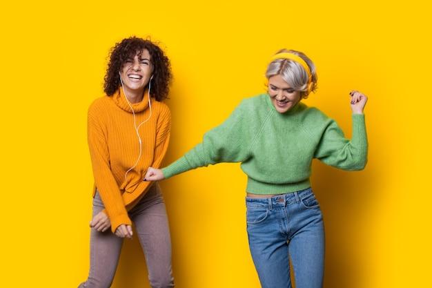 Twee vrolijke zusters met krullend haar luisteren naar muziek en glimlachen op een gele muur met vrije ruimte met behulp van een koptelefoon