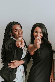 Twee vrolijke zwarte vrouwen wijzend op een camera