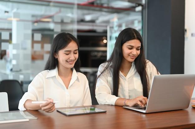Twee vrouw workwer werkt via een laptop op een modern kantoor