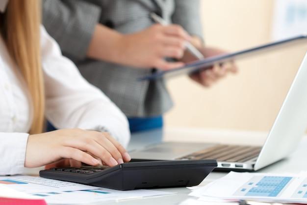 Twee vrouwelijke accountants die op calculatorinkomen rekenen voor de close-up van de voltooiingshanden van het belastingformulier.
