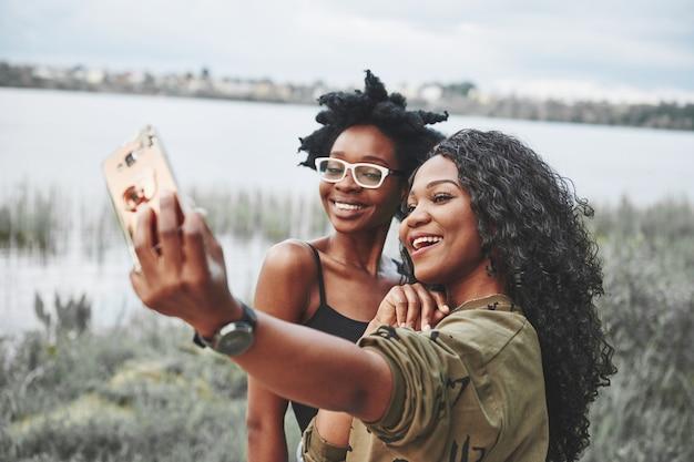 Twee vrouwelijke afro-amerikaanse vrienden hebben een wandeling rond het strand. selfie maken.