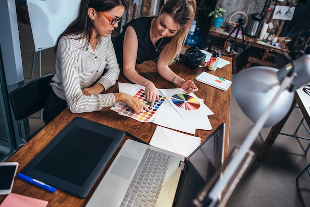 Twee vrouwelijke architecten werken samen met behulp van kleurstalen zittend aan een bureau met laptop.