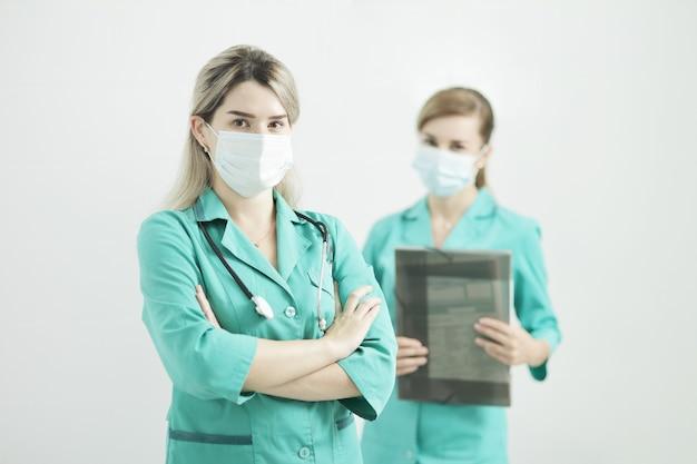 Twee vrouwelijke arts of verpleegster die medische maskers dragen die de camera bekijken.