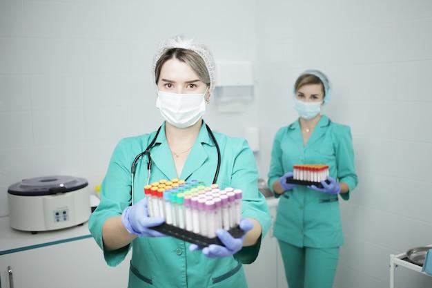 Twee vrouwelijke artsen in medisch masker houden bloedonderzoekbuizen
