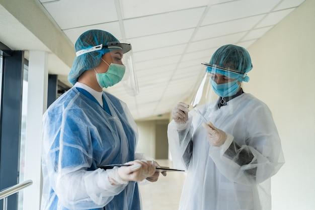 Twee vrouwelijke artsen met beschermende kleding houden een reageerbuis met bloedmonster vast aan het coronavirus in een moderne kliniek. covid-19-pandemie
