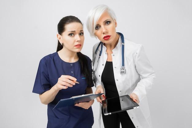 Twee vrouwelijke artsen met tablet en blad met analyse in handen die op wit worden geïsoleerd